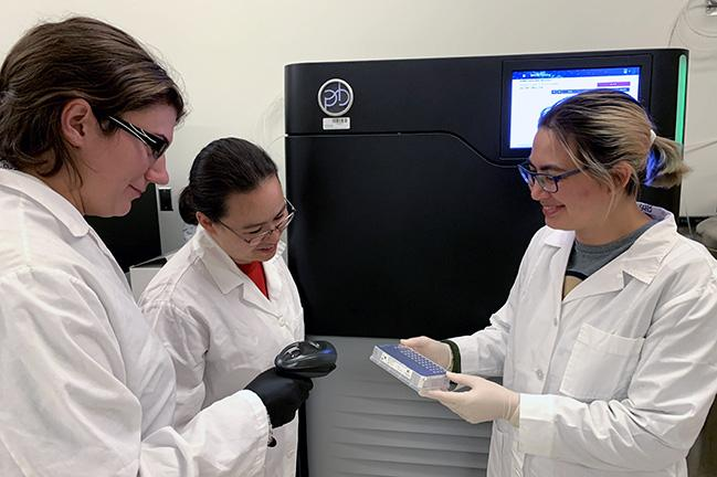 UW genome science technicians Melanie Sorensen, Katherine Munson and Alexandra Lewis at the PacBio Sequencing Services with a microtiter plate for the Sequel II instrument in the background. Image credit: Amy B. Wifert/Washington University in St. Louis