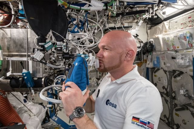 Astronaut Alexander Gerst exhales into an ultra-sensitive gas analyzer for the Airway Monitoring experiment. Credits: NASA