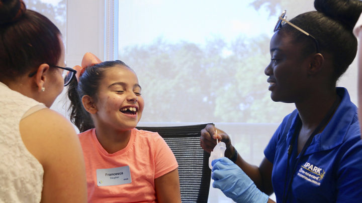 Nichelle Decius, a member of the UM-NSU CARD's research staff, takes a saliva sample from a girl who is enrolling in the SPARK study.   Image credit: University of Miami