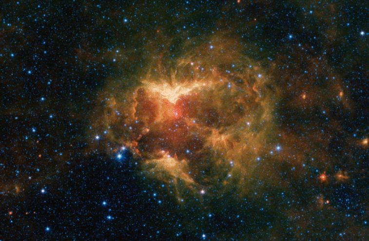 """This infrared image from NASA's Spitzer Space telescope shows a cloud of gas and dust carved out by a massive star. A drawing overlaid on the image reveals why researchers nicknamed this region the """"Jack-o'-lantern Nebula."""" Credits: NASA/JPL-Caltech"""