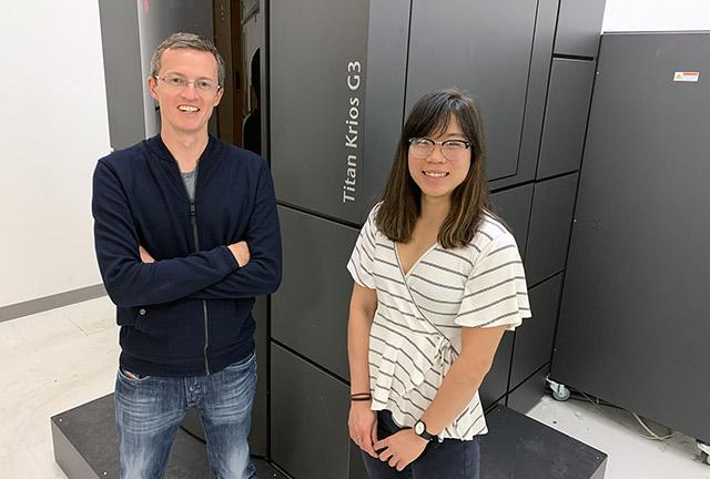 Henipavirus antibody researchers David Veesler and Ha Dang in front of a Titan Krios electron microscope at the Arnold and Mabel cryoEM Center at UW Medicine. Image credit: Veesler lab