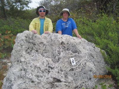 Co-author Kristine DeLong and a colleague stand behind a fossilized coral reef boulder dating back to the last interglacial that washed ashore on Little Cayman. Courtesy of Kristine DeLong, Louisiana State University