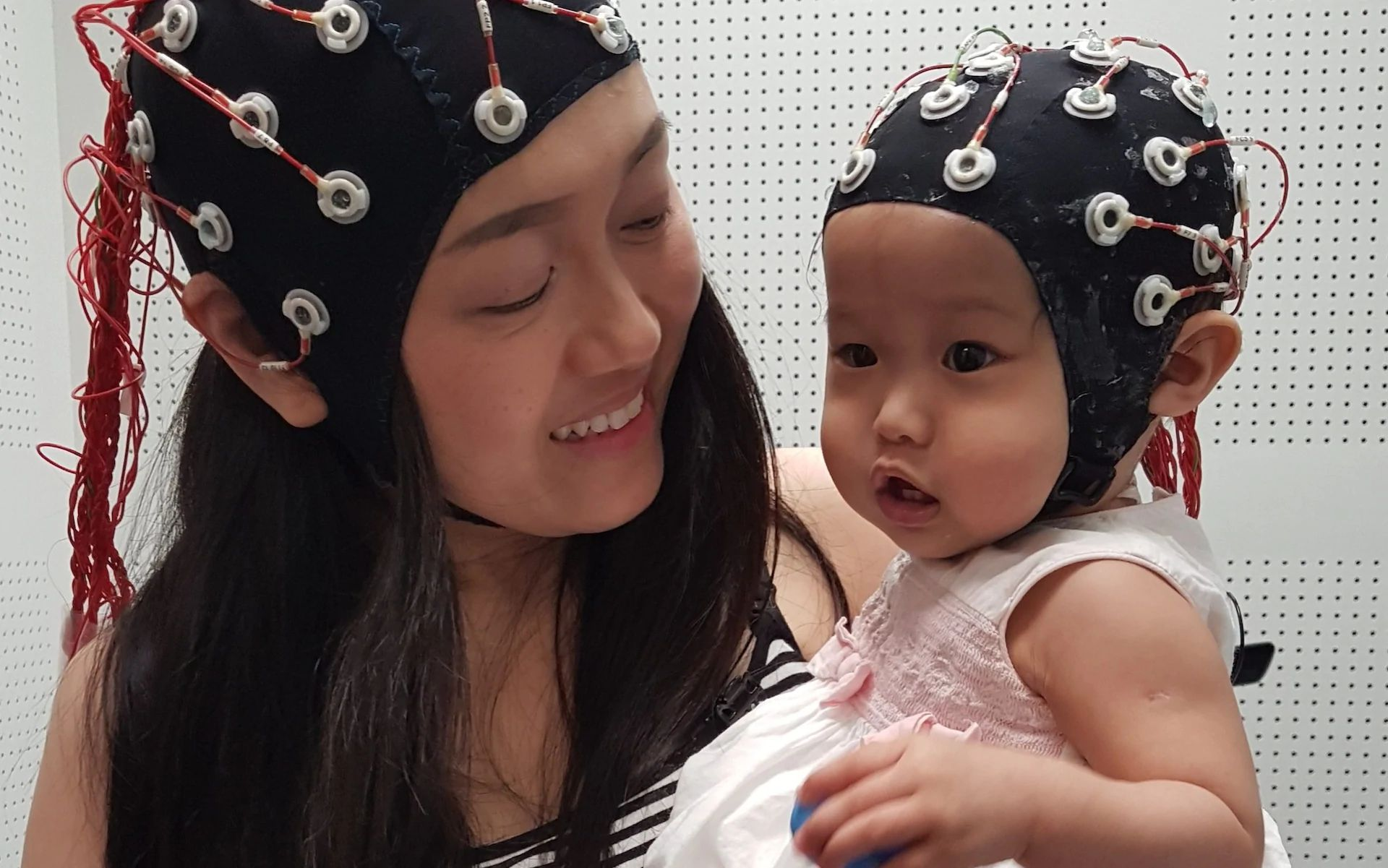 Woman with a child wearing dual electroencephalograhy on they heads. Image credit: University of Cambridge