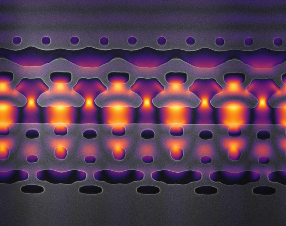 This image, magnified 25,000 times, shows a section of an accelerator-on-a-chip. The gray structures focus infrared laser light (shown in yellow and purple) on electrons flowing through the center channel. By packing 1,000 channels onto an inch-sized chip, Stanford researchers hope to accelerate electrons to 94 percent of the speed of light. Image credit: Courtesy Neil Sapra/Stanford University