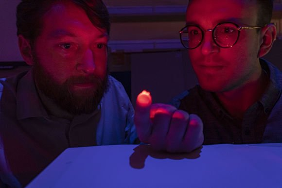 two men, with one holding a tiny device with a bright light on his fingertip